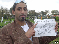 Naseed Sadiq with a note he found near the vandalised graves