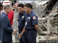 Prince Charles talks with New Orleans Fire Fighters Autrey Plaisance (C) and Kevin Harrel on a tour to survey the damage to the Lower Ninth Ward