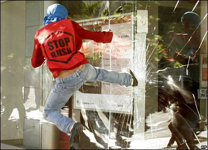 A protester kicks in a window of a bank