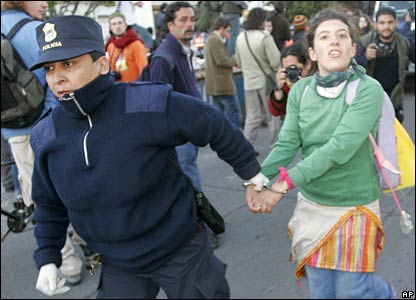 A policewoman arrests a protester