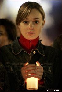 Una chica sostiene una vela en la Plaza de San Pedro del Vaticano.