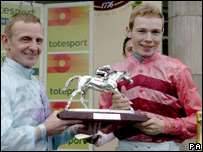Jamie Spencer (right) receives the trophy from former champion Kevin Darley