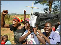 Zanu-PF party supporters carry a mock coffin representing the opposition MDC
