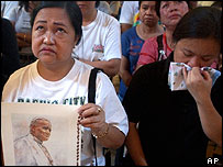 Mourners in Philippines with picture of the Pope