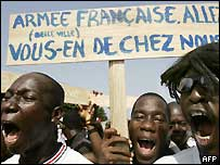 Demonstrators in Ivory Coast holding up a sign calling for the French peacekeepers to go home