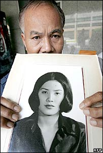 Thai villager, Sukham Panjoy, 59, (L) shows a portrait of his sister Anocha Panjoy at the Foreign Ministry in Bangkok, 07 November 2005,