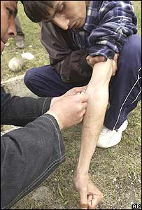 A Kyrgyz drug addict makes a heroin injection to another drug addict in Osh, southern Kyrgyzstan, Friday, March 25, 2005.