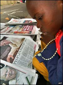 A Nigerian child reads newspapers carrying pictures of John Paul II