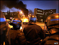 Riot police wait near Toulouse district of Le Mirail as bus burns