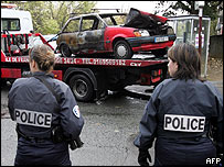 Women police officers watch scorched car being removed from Grigny street
