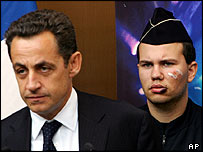French Interior Minister Nicolas Sarkozy speaks beside unidentified injured policeman in Evreux