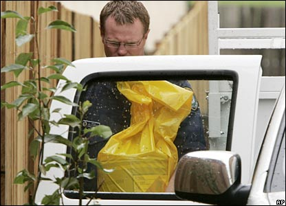A forensic officer takes a bag from a raided apartment block in Sydney