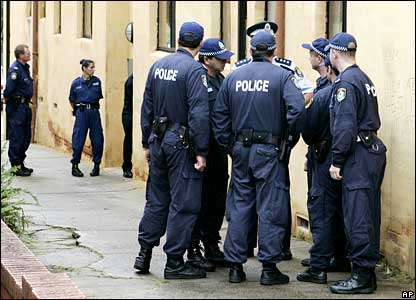 Police stand outside a raided apartment block in Sydney