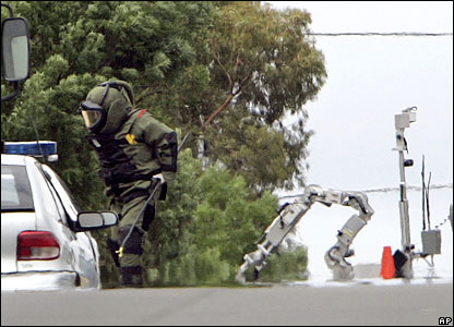 A policeman in a protective suits examines suspect vehicles with a robot back-up