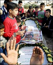 Palestinian children mourn at the grave of Ahmed Ismail Khatib