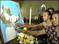 East Timorese women touch a picture of the Pope