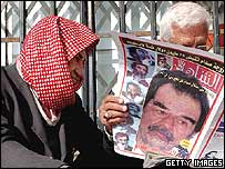 An Iraqi man reads a newspaper plastered with an image of Saddam Hussein in Baghdad, December 2004