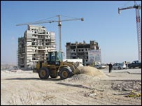 Bulldozers help construct additions to the settlement