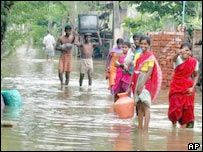 Residents carry their belongings through flood waters in the outskirts of Madras