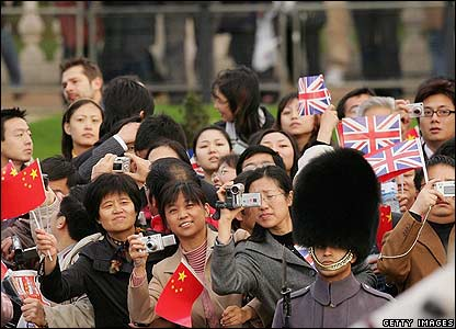 Chinese people watch as President Hu Jintao and the Queen are driven past them
