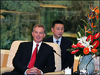 An interpreter sits behind Tony Blair during a visit to China