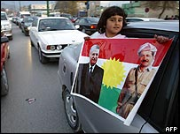Kurdish girl carries poster showing Talabani and Barzani