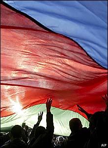 Protesters huddle under a huge national flag