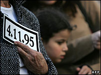 Mourner holds card showing date of Yitzhak Rabin's assassination