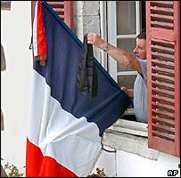 Man attaches black ribbon to French tricolour
