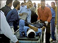 A wounded policeman is taken into a hospital in Baquba