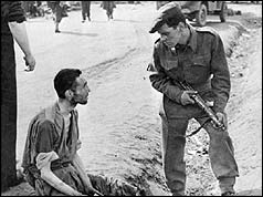 British soldier talks to an inmate at Belsen concentration camp