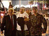 An injured man is escorted from the Grand Hyatt hotel in Amman, Jordan