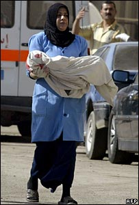 An Iraqi nurse carries the body of an Iraqi boy who was killed along with his father at a Baghdad restaurant
