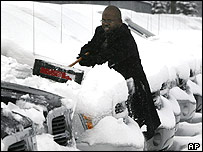 A sales consultant in Detroit clears snow off a Dodge Durango