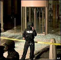 A Jordanian policeman guards the shattered front of the Hyatt hotel in Amman
