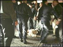 People help an injured man outside the Hyatt hotel, Amman