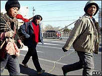 A group of peasants pull a cart filled with their belongings and wood to build a makeshift hut, as they make their way into Beijing 10 January 2003,