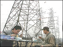 Chinese eat lunch at a food stall below power lines in Beijing Monday March 21, 2005