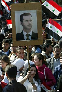 A Syrian woman waves a picture of president Bashar al-Assad as he delivered his speech