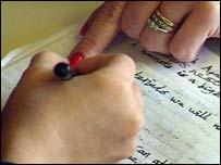 Woman's finger pointing at child's hand-writing