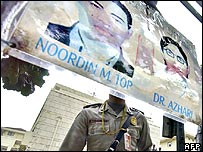 An Indonesian policeman stands behind a gate with pictures of fugitive main suspects of several bombings in Indonesia, Malaysians Noordin M Top and Azahari Husin displayed in Jakarta, 26 October 2005.