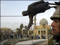US soldier stands by toppled statue of Saddam Hussein in central Baghdad, 9 April 2003