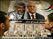 Palestinians look at posters of Yasser Arafat and Mahmoud Abbas