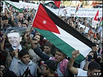 People march in Amman carrying the Palestinian flag and a picture of King Abdullah