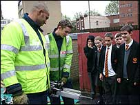Firefighters demonstrating cutting equipment to pupils
