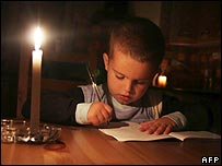 Boy does homework by candlelight in Tirana