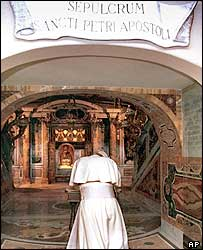 Pope John Paul II prays in front of the tomb of St Peter, revered as the first pope