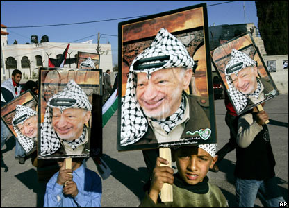 Children carry posters of Yasser Arafat