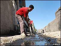 An Iraqi man cleans a flooded street in the impoverished Sadr city neighborhood of Baghdad, Iraq