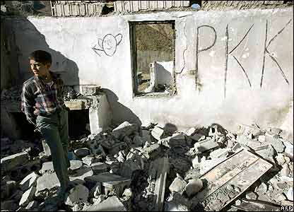 Boy stands by PKK graffito in Semdinli